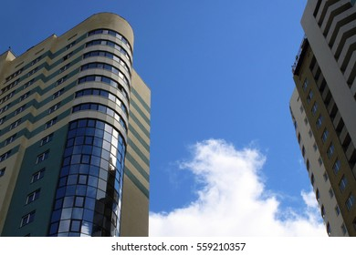 Bottom view of modern skyscrapers against blue sky with clouds