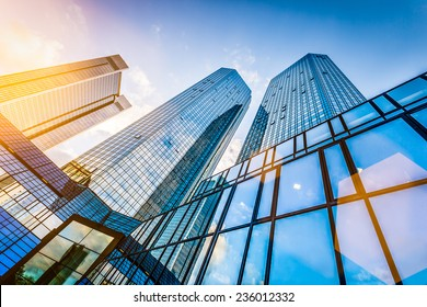 Bottom view of modern skyscrapers in business district in evening light at sunset with lens flare filter effect