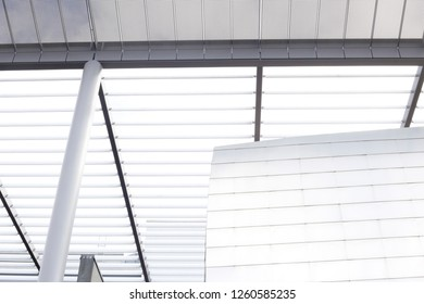 Bottom view of office building exterior fragment with metal girders, pillars and jalousie / louvers / blinds. Abstract close-up photo of modern architecture, construction industry or technology.