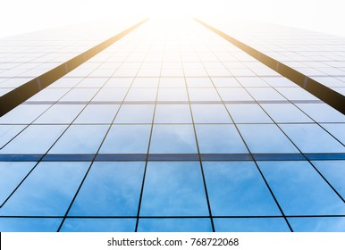 Bottom view of office building window close up with sunrise, reflection and perspective.