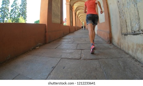 bottom view of people footing in San Luca Sanctuary archway, the longest porch in the world leading to Bologna city downtown, north Italy.