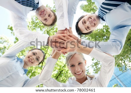 Bottom view of people making pile of hands on background of green foliage