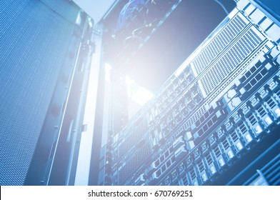 Bottom view of rack server storage and network against neon light in data center with dept of field in blue cool tone , technology background
