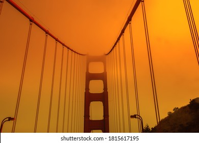 Bottom view of smoky orange sky on Golden Gate Bridge of San Francisco city from bottom view. California fires in United States of America. Composition about wildfires and climate change concept.