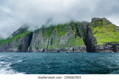 Bottom view of the spectacular Vestmanna cliffs under the mist in the Faroe Islands