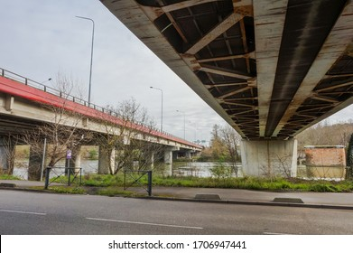 Bottom view of the steel truss girders of the railway viaduct of Empalot over the River Garonne in Toulouse, France, featuring some rust stains, seen from Chemin de la Loge Road on the embankment