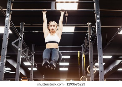 Bottom view - a strong athletic young champion female fitness bloger works with her own weight on the bar. The concept of building a slim body