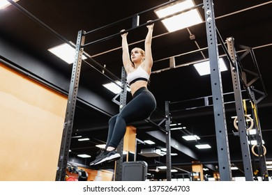 Bottom view - a strong athletic young champion girl fitness bloger works with her own weight on the bar. The concept of building a slim body