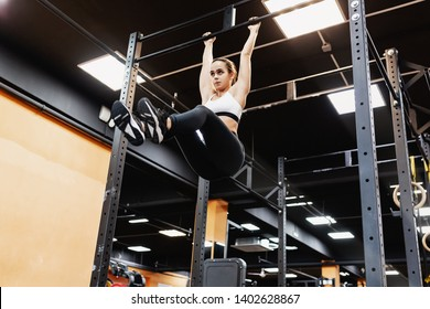 Bottom view - a strong athletic young champion woman fitness bloger works with her own weight on the bar. The concept of building a slim body