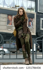 Bottom view of a stylish girl who demonstrates clothes against the background of a stream of cars She is dressed in a boho style: brown coat, yellow bag, green sweater, shorts and torn stockings