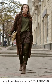 Bottom view of a stylish girl who walks on the sidewalk on the background of historic buildings. She is dressed in a boho style: brown coat, yellow bag, green sweater.