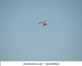 A bottom view super lightweight hang glider or trike flies in clear blue sky