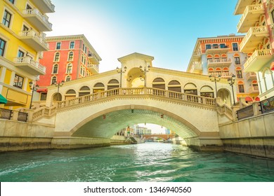 Bottom view of venetian bridge overlooking canals of picturesque Qanat Quartier icon of Doha, Qatar. Little venice at the Pearl, Persian Gulf, Middle East. Famous tourist attraction.