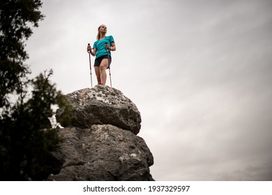 bottom view of woman traveler with trekking poles standing on large stone against the sky