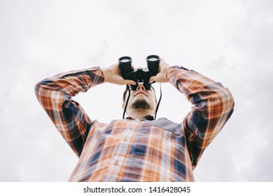 Bottom view of young man in plaid shirt watching with binoculars and exploring surroundings on white background of sky. Travel concept.