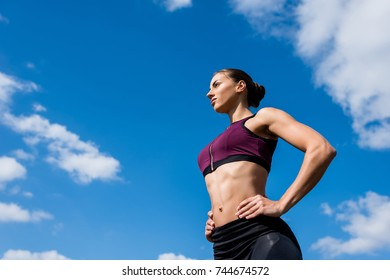 bottom view of young sporty woman in front of blue sky