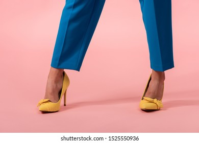 bottom view of young stylish disco girl in yellow heeled shoes and blue trousers on pink background