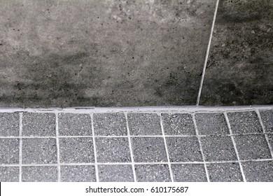Bottom wall floor corner cracked shower tile grout in need of resealing split. Cracked bathroom shower tile grout corner between wall and floor that needs repaired.