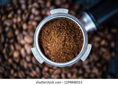 Bottomless filter with grind beans on a wooden black table. Roasted coffee beans. Espresso coffee extraction. Prepare of espresso.