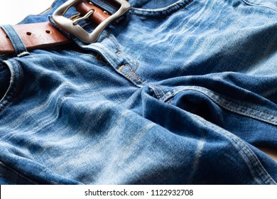 Bottoms of denim jeans and brown leather belt