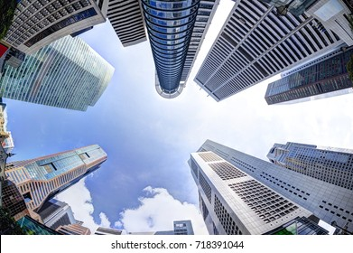 Bottoms-up view of business office skyscrapers and highrise buildings in Singapore's business and financial district at Raffles Place. Fisheye shot of rising architecture into blue and cloudy skies.