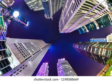 A bottom-up night view of a group of buildings in a business district in Singapore with fish eye lens