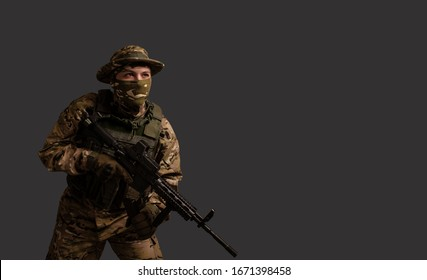 A bottom-up portrait view of a soldier in a military camouflage uniform wearing a  helmet, body armour, and holding a machine gun on a gray background.  Sniper. Army banner.  Border guard.