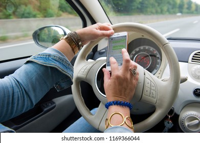 BOTTROP, GERMANY - AUG 16, 2018: A blond woman is whatsapping on her smartphone while she is driving on a highway in full speed.