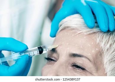 Botulinum Toxin Injections. Beautiful natural looking senior woman with short gray hair receiving Botulinum Toxin Injections.