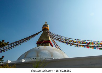 The Bouddhanath Temple in Kathmandu, Nepal. The temple has many colourful prayer flags with 'om mani padme hum' mantra written on them attached to it's golden rooftop. Spirituality and meditation.
