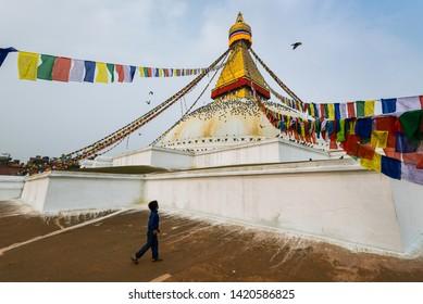 Boudhanath stupa, Kathmandu, Nepal - April 2019, Nepali boy is looking at the buddha eyes of Boudhanath stupa in the morning