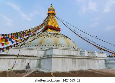 Boudhanath stupa, Kathmandu, Nepal - April 2019, a lady was doing meditation in the morning beside Boudhanath stupa as normal Buddhism activity