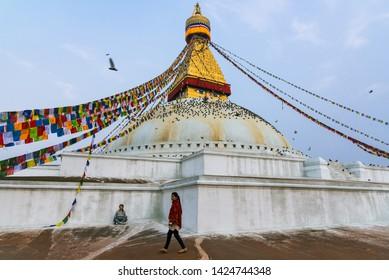 Boudhanath stupa, Kathmandu, Nepal - April 2019, a lady had done her meditation beside Boudhanath stupa while the tourist was walking around in the morning.