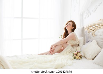 Boudoir Bride's morning. Cute red-haired girl in her wedding day. Gentle but sexy young beautiful woman in a negligee preparing for her wedding day on a bed. Luxurious bride in a beautiful lace robe