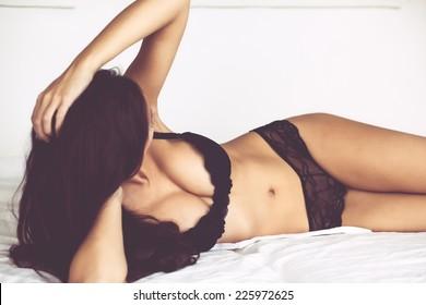 Boudoir photo of sexy girl wearing stylish black lingerie underwear posing on white bed