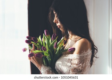Boudoir photography of a beautiful brunette girl with long hair. Flowers tulips in the hands of a beautiful woman. Portrait in the genre of boudoir. Photo shoot in underwear, femininity.