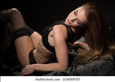 Boudoir photography of a beautiful young woman over dark background