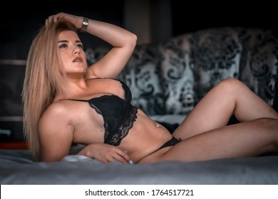 Boudoir and sexual photograph of a young blonde Caucasian woman in black lingerie on top of a round bed with a black flower headboard. Lying in bed with sexy posture. With sexual gaze
