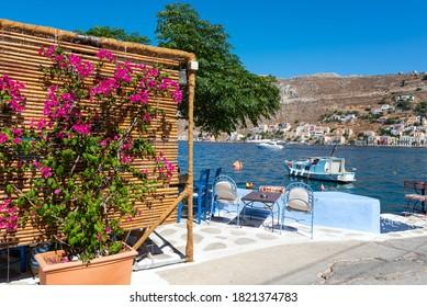 Bougainvillea flowers in street cafe, located near blue lagoon at Symi island, Greece