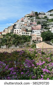 Bougainvillea spreads across a roof in front of the colourful houses of Positano stacked on a precipitous hillside, Italy