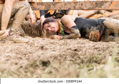 Boughton House, Northamptonshire/UK - May 31, 2015: A participant rolls through the Kiss of Mud obstacle at the Tough Mudder extreme sport challenge raising funds for Help for Heroes.