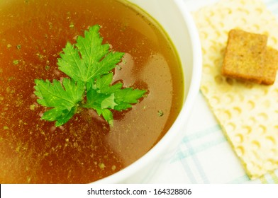 Bouillon, broth, clear soup in a white cup with a loaf, parsley on the tablecloth. Close-up.