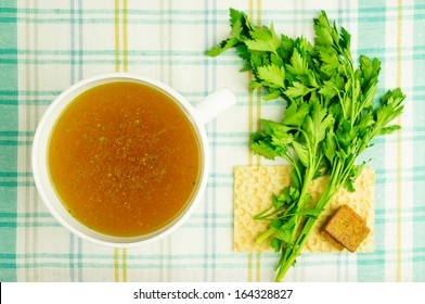 Bouillon, broth, clear soup in a white cup with a loaf, parsley, boiled egg on the tablecloth. Close-up.