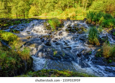 """Boulaide, Wiltz, Luxembourg - September 27, 2018: Water from the upper Sure River tumbles over the falls at the """"Bauscheltermillen"""" in the Upper Sure Natural Park"""
