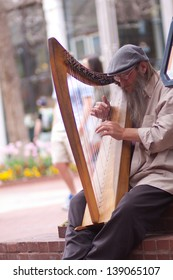 BOULDER, CO - MAY 18, 2013:  Street musician playing classical harp to entertain tourists on the Pearl Street Mall in Boulder, CO on May 18, 2013.