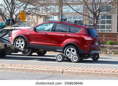 Boulder, CO USA - May 5, 2021: Impounded car being towed with a towing dolly. Tiny wheels under back wheels