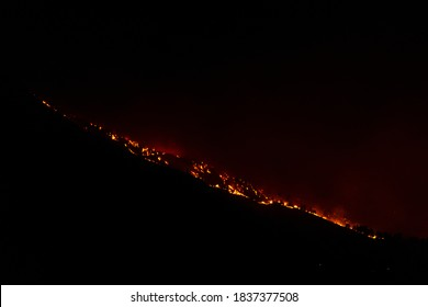 BOULDER, CO, USA - OCTOBER 17, 2020: Fires from the Cal Wood fire, the largest wildfire in Boulder County history, burn into the night on the foothills and neighborhoods on the Front Range