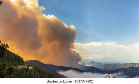 BOULDER, CO, USA - OCTOBER 18, 2020: A plume of wildfire smoke rises into the sky from the Left Hand Canyon just hours after the Left Hand Canyon fire broke out in Boulder, Colorado.