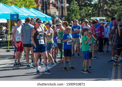 Boulder, Colorado / United States of America - September 8th, 2019 : A runner strikes a pose in a group of people waiting for the start of the Rainbow Run Walk 5k, part of Boulder Pridefest.