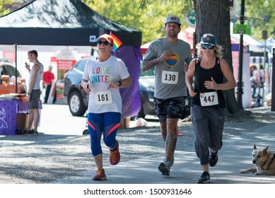 Boulder, Colorado / United States of America - September 8th, 2019 : Three runners approach the finish line of the Rainbow Run Walk 5k, part of Boulder Pridefest.